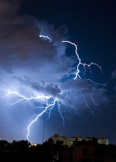 Picture of atmospheric lightening striking ground near a building at night